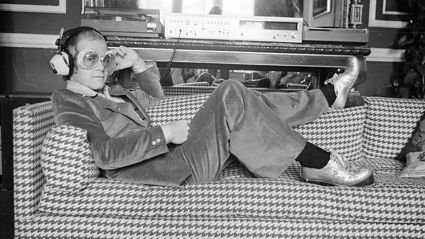 12th September 1974: English pop star Elton John relaxes on a sofa and listens to some music. (Photo by D. Morrison/Express/Getty Images)