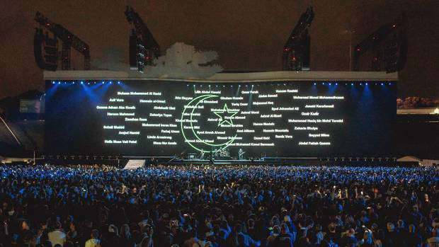 The names of the 51 people killed in the Christchurch mosque shootings were reflected on the screen while the Irish band played 'One' / NZ Herald / Stewart Sowman-Lund